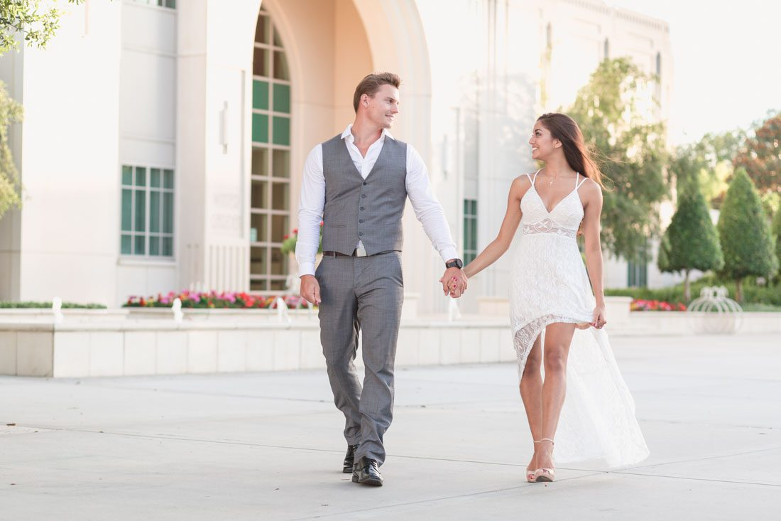 Gorgeous couple walking in front of City Hall in historic Winter Garden during their engagement photography shoot with top Orlando wedding photographer and videographer