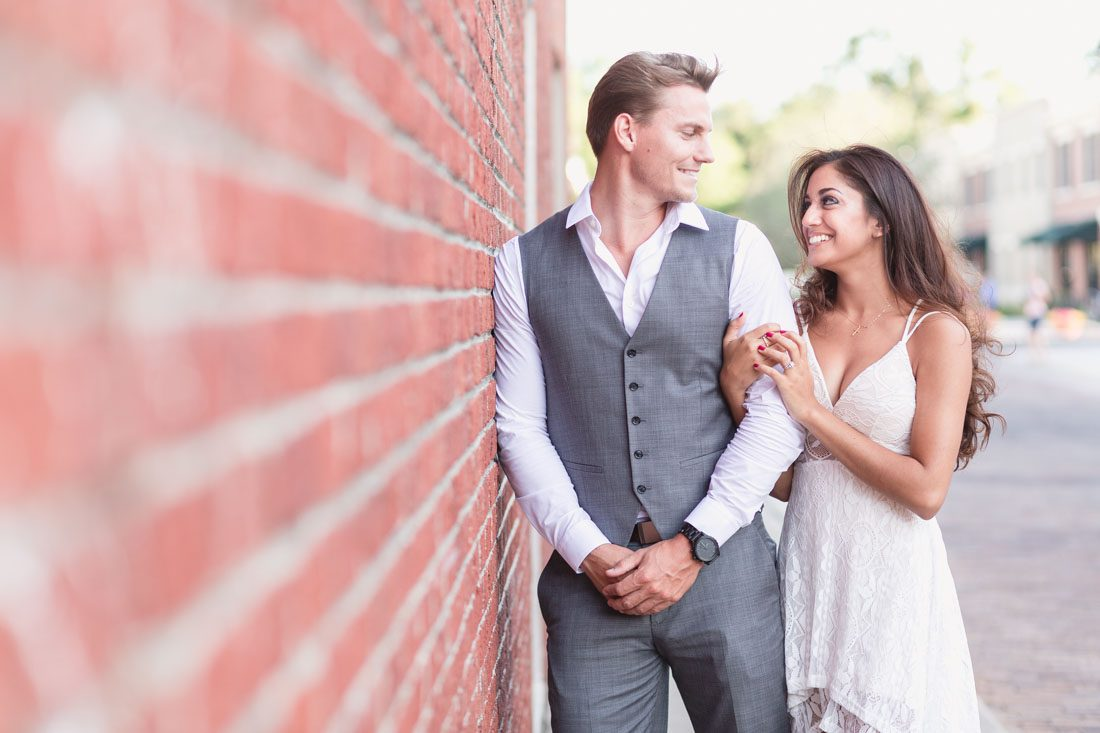 Romantic engagement photography session in historic downtown Winter Garden on a red brick wall captured by top Orlando wedding photographer and videographer