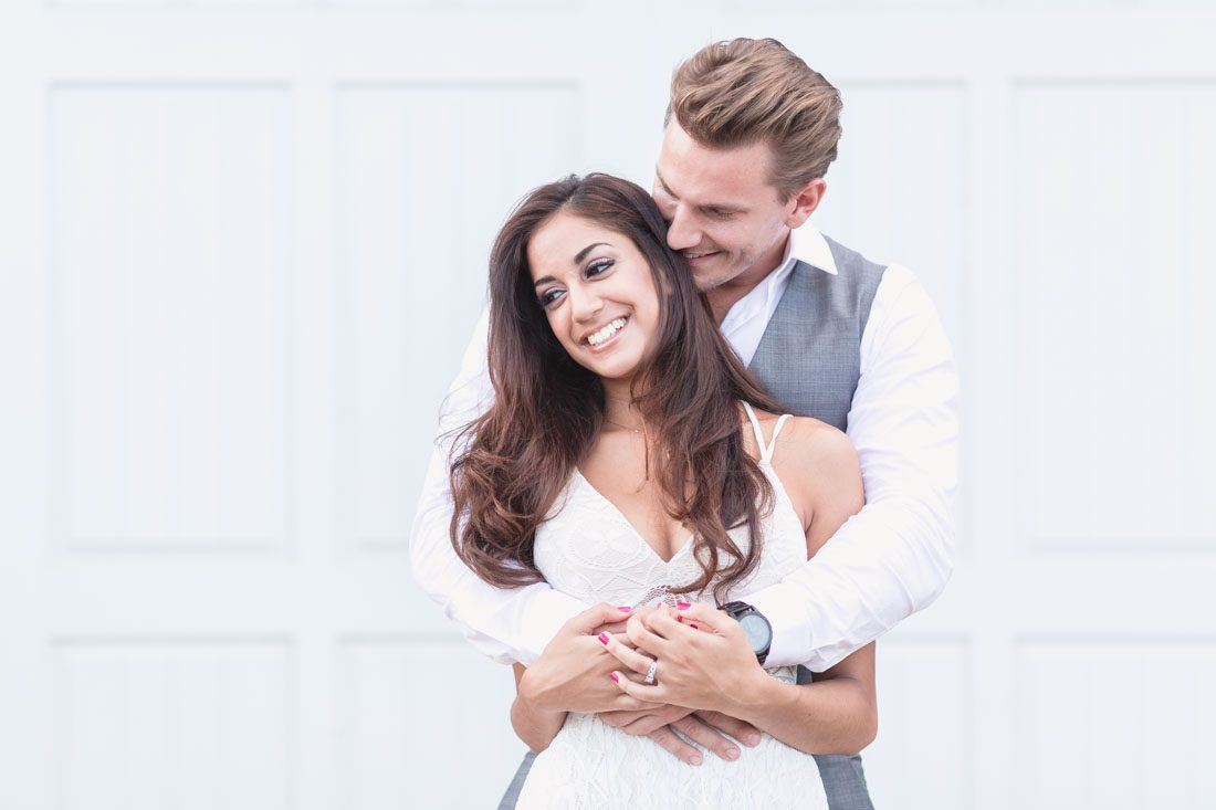 Romantic engagement photo with couple embracing in front of a white wall in historic downtown Winter Garden during their engagement portrait session with top Orlando wedding photographer
