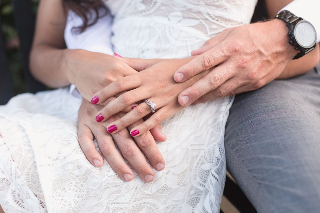 Close up of the future bride's engagement ring with her fiance during their engagement portrait session in Winter Garden, Florida
