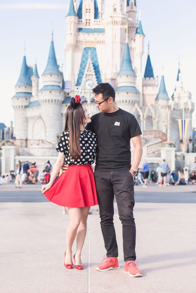 Engaged couple in front of the Walt Disney World Cinderella castle in Orlando for a fun photo shoot with top photographer