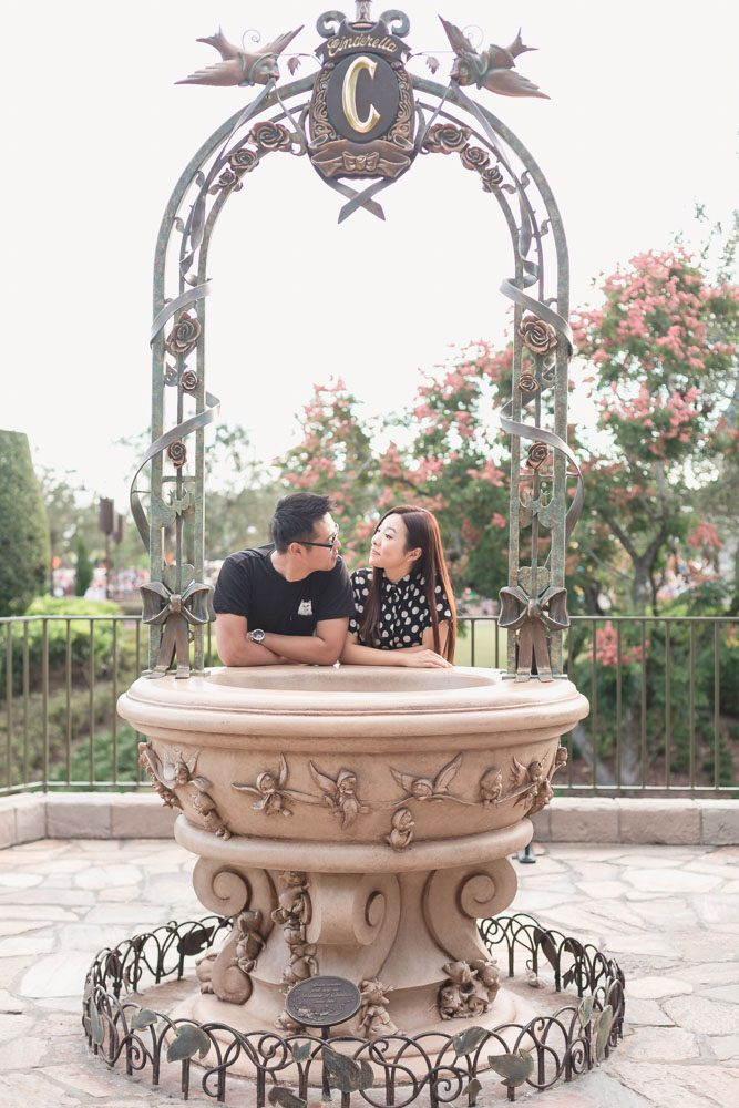 Married couple in front of the fountain at Cinderella's castle at Disney world during their anniversary photo shoot with top Central Florida photographer