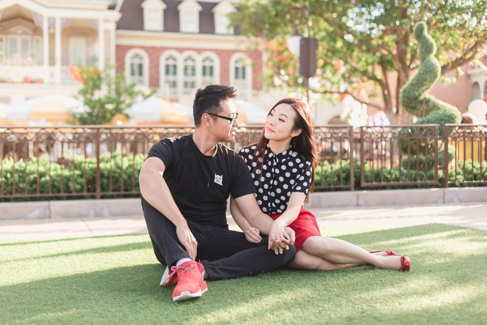 Married couple sitting in the grass at Disney's Magic Kingdom park during their photo shoot with Captured by Elle Photography in Orlando, Florida