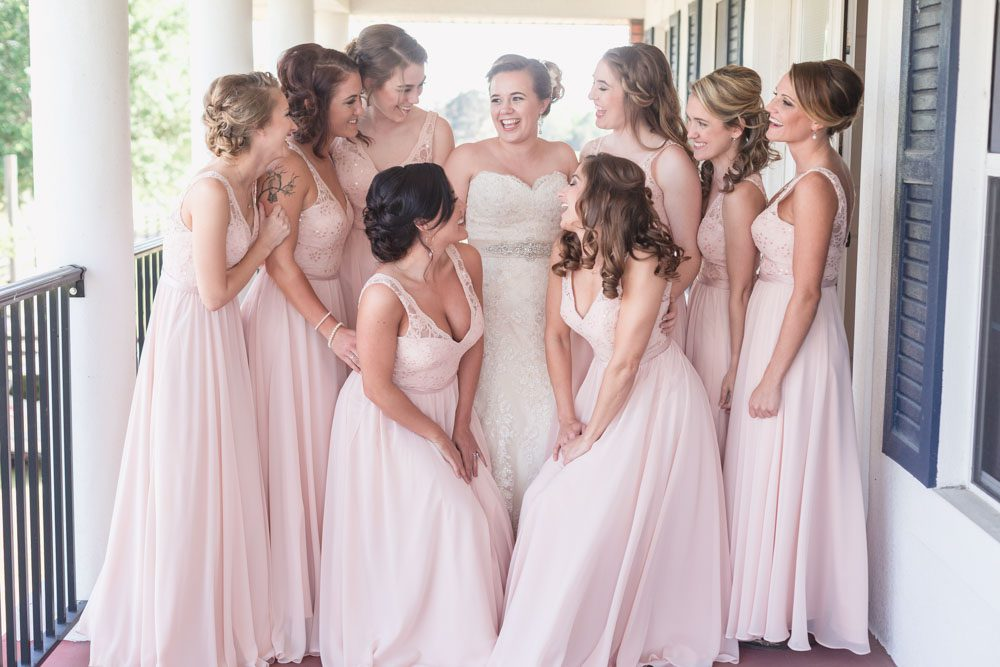 Bride getting ready with her bridesmaids featuring blush dresses for their country wedding day at a barn in Central Florida
