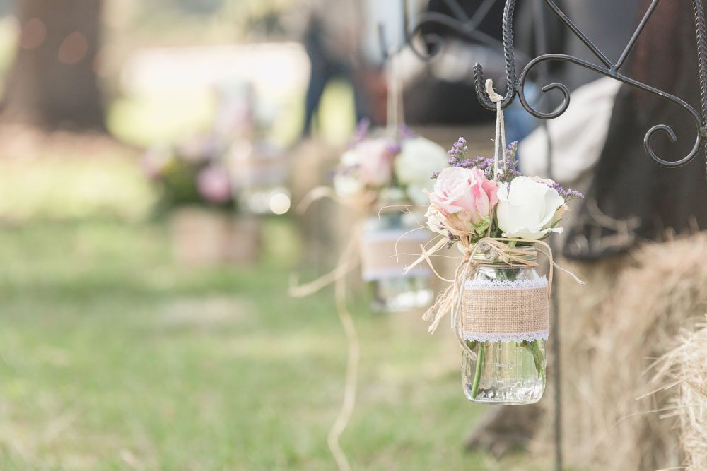 Rustic country decor featuring mason jars and burlap alongside hay bales for an outdoor wedding in central Florida