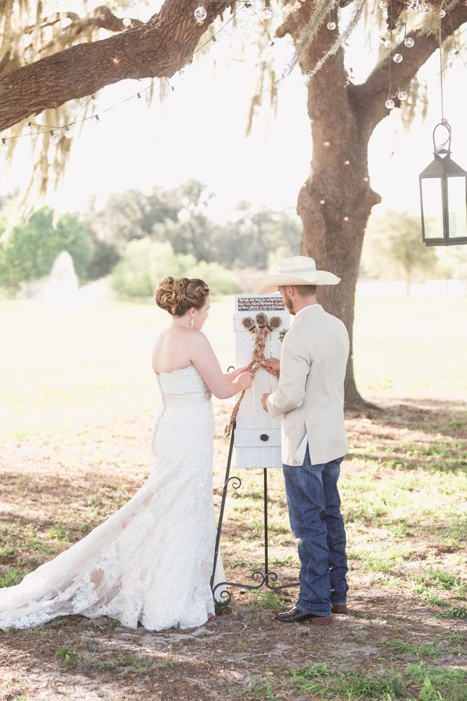 Couples ties a cord of three strands during their country wedding ceremony outdoors under a tree at a farm in Central Florida