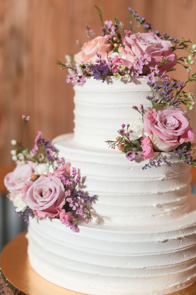 Rustic country wedding cake with buttercream on a tree trunk wooden cake stand