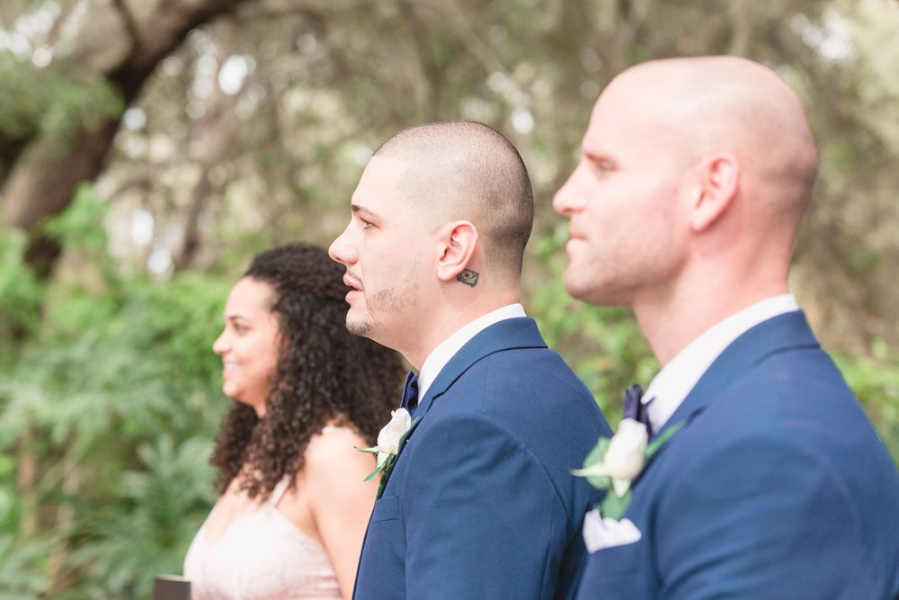 Groom's emotional reaction to seeing the bride down the aisle during their outdoor wedding ceremony in Kissimmee captured by top Orlando wedding photography team