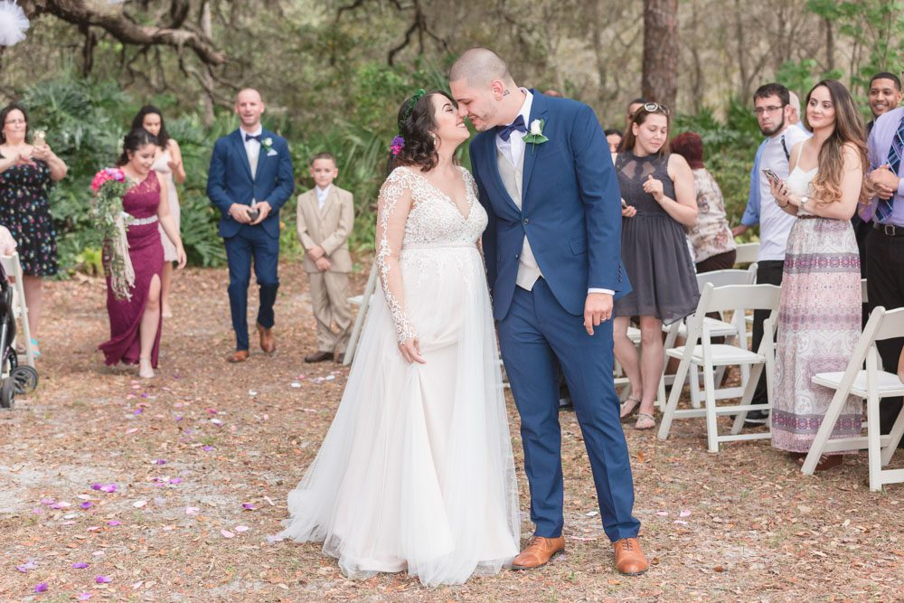 Newlyweds kiss during their outdoor wedding ceremony under a tree during their Central Florida wedding day
