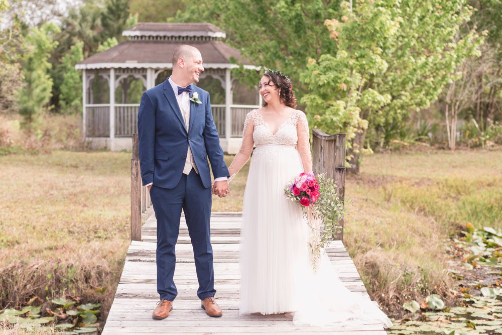 Bride and groom portrait on a dock during their romantic intimate backyard wedding day in Kissimmee Florida captured by top Orlando wedding photographer and videographer