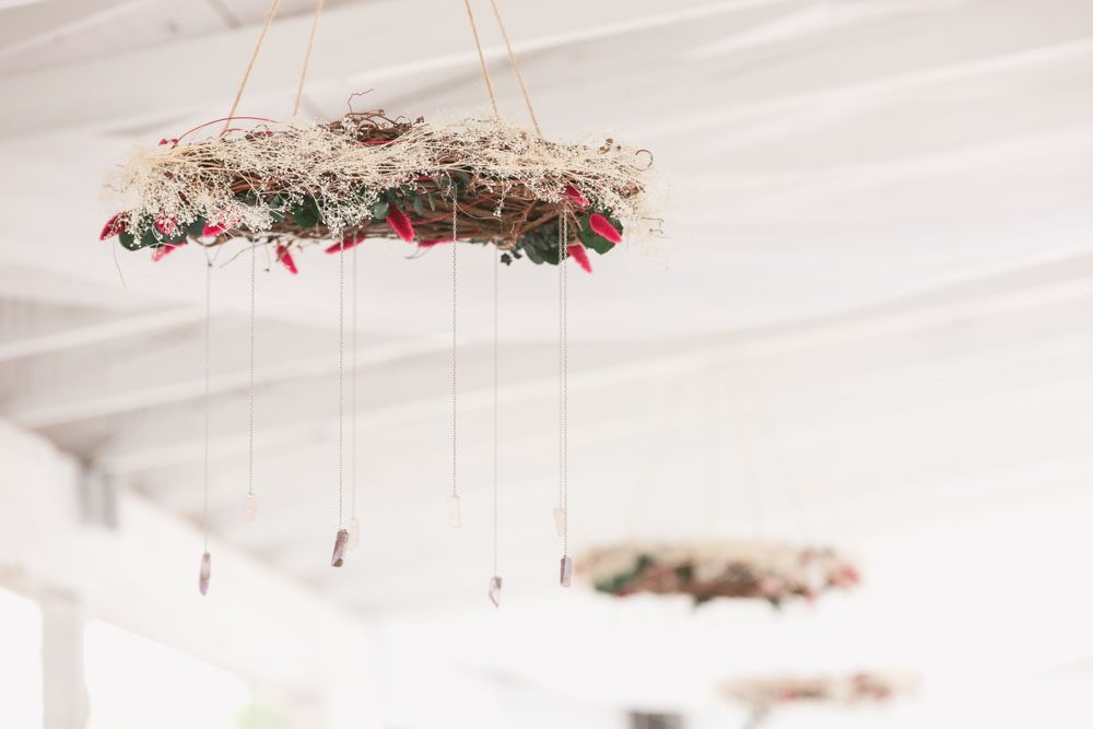 Gorgeous DIY handmade wreath chandeliers with rock crystals and flowers hung above guest tables in a beautiful outdoor wedding reception in Kissimmee, Florida captured by top Orlando wedding photographer