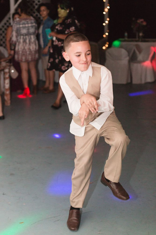 Fun action shot on the dance floor photo of the ring bearer during the reception at an intimate wedding day in Kissimmee captured by top Orlando wedding photographer