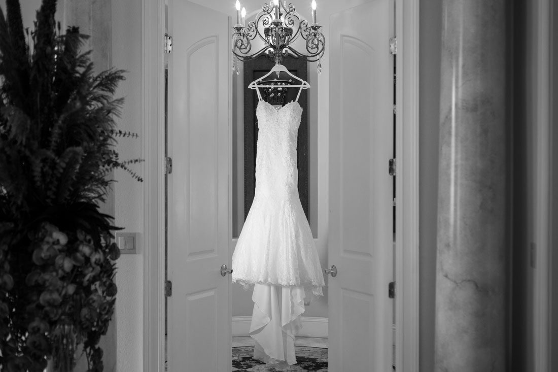 Brides dress hanging captured by top Orlando wedding photographer and videographer
