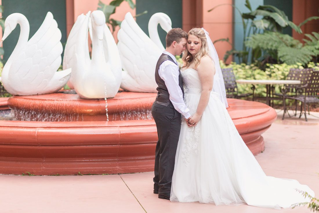 Same sex couple poses in front of the swan statues at Disney's swan and dolphin resort wedding