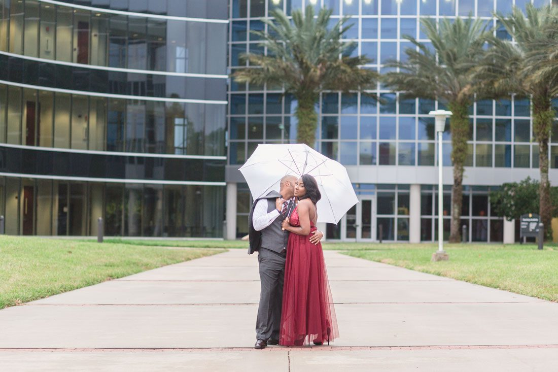 Couple poses with an umbrella during rain at their engagement session