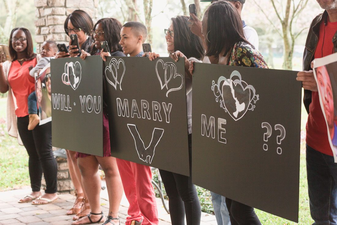 Family and friends hold signs and read will you marry me in a surprise proposal