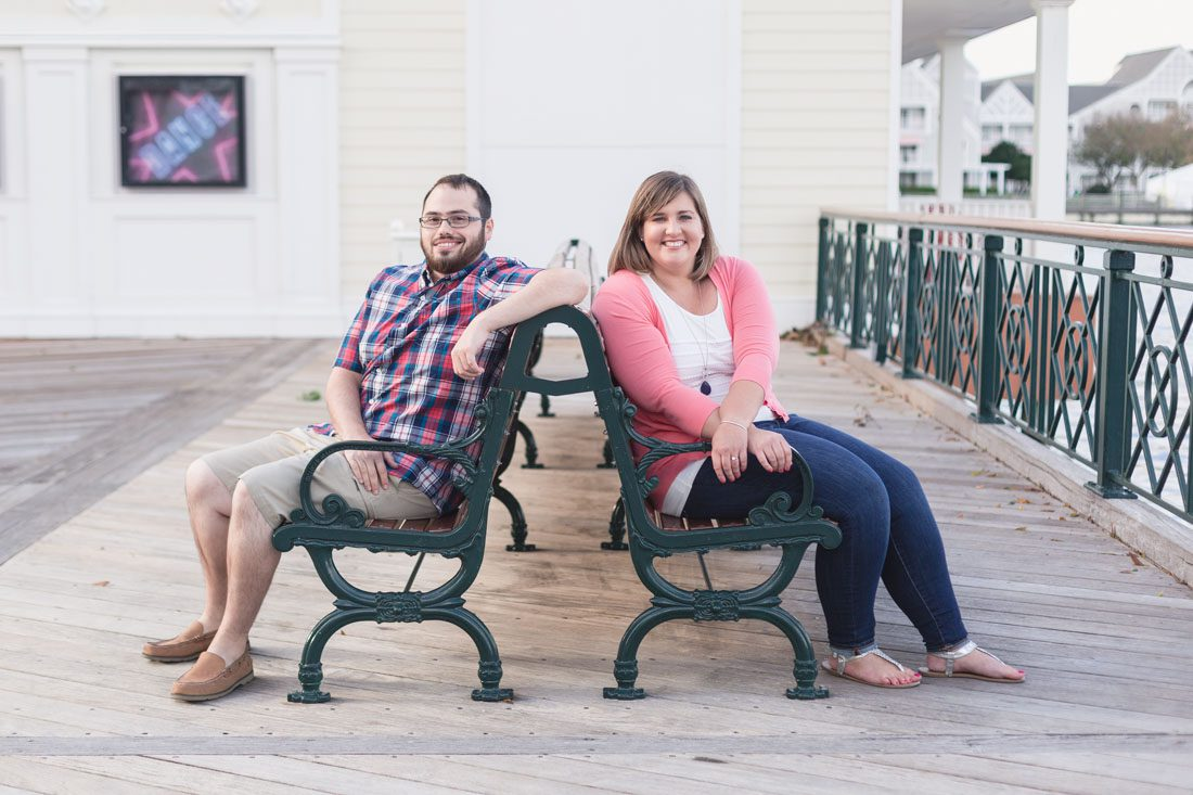 Newly engaged couple sitting on a bench for their engagement photography session at Disney Boardwalk