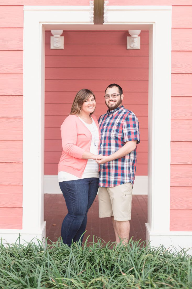 Couple posing for engagement photos by top Orlando photographer at Disney Boardwalk