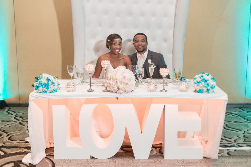 Couple at their wedding reception seated at a LOVE table at the Gaylord Palms
