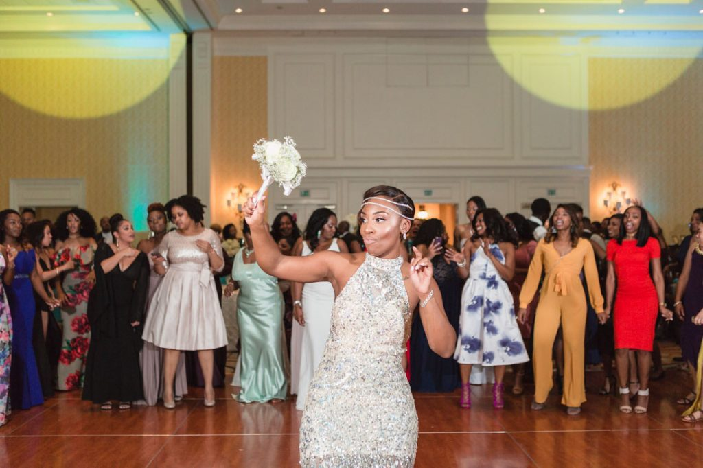 Bride throwing the bouquet at her Orlando wedding captured by top photographer Captured by Elle