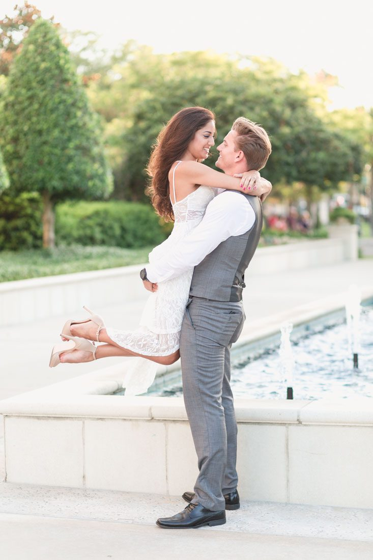 Romantic engagement photo with couple embracing in front of a fountain in historic downtown Winter Garden during their engagement portrait session with top Orlando wedding photographer