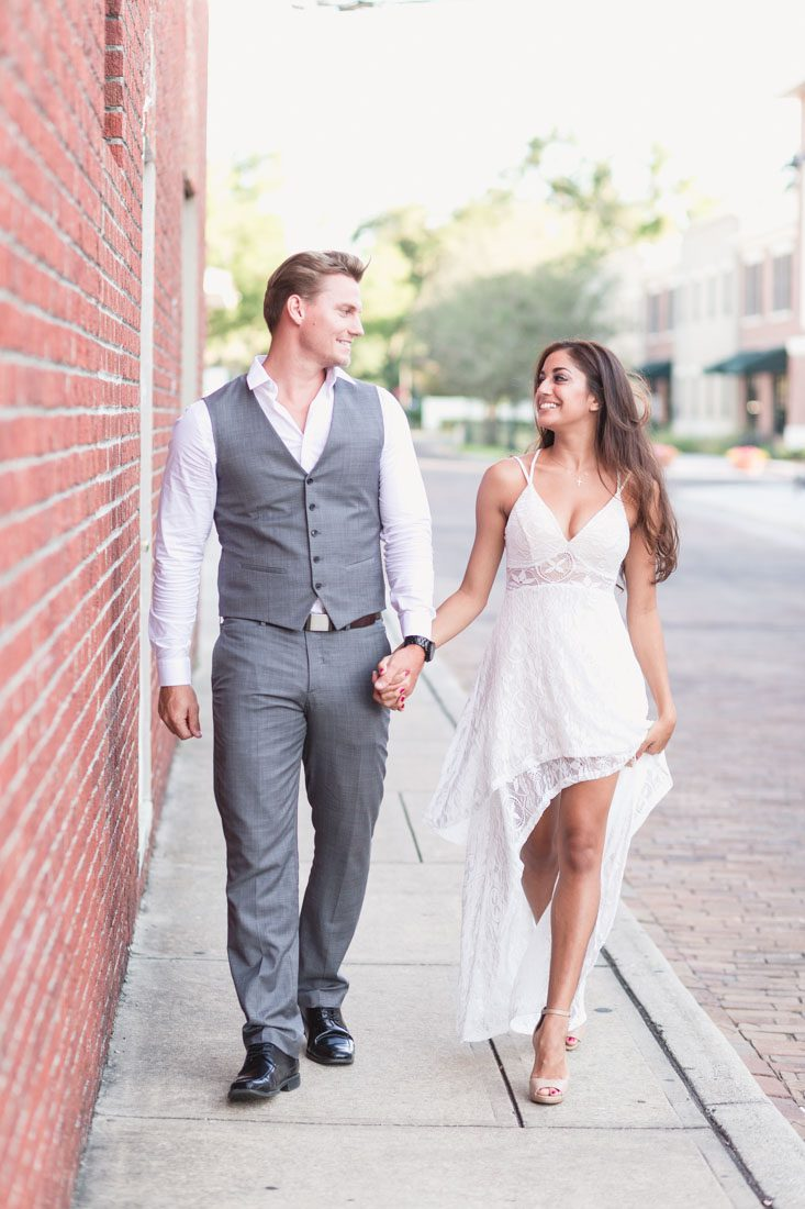 Engaged couple walks along a red brick wall in historic Winter Garden just west of Orlando during their engagement photography shoot