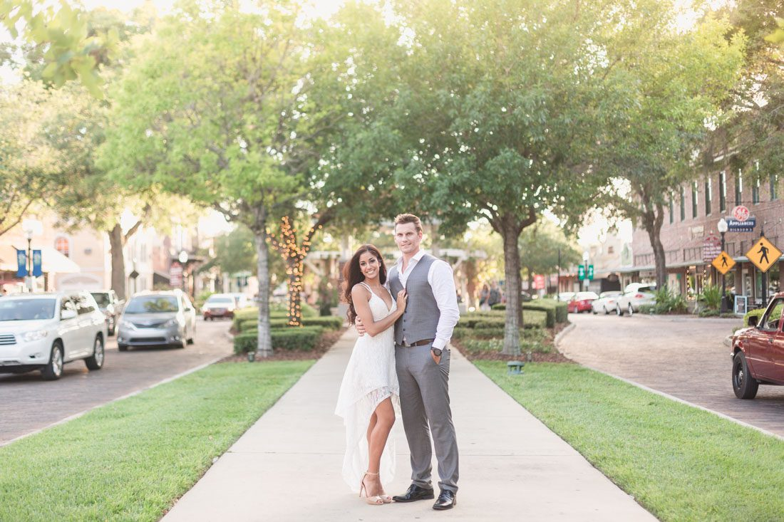 Engagement photos along a tree lined street in the charming historic town of Winter Garden, Florida captured by top Orlando wedding photographer