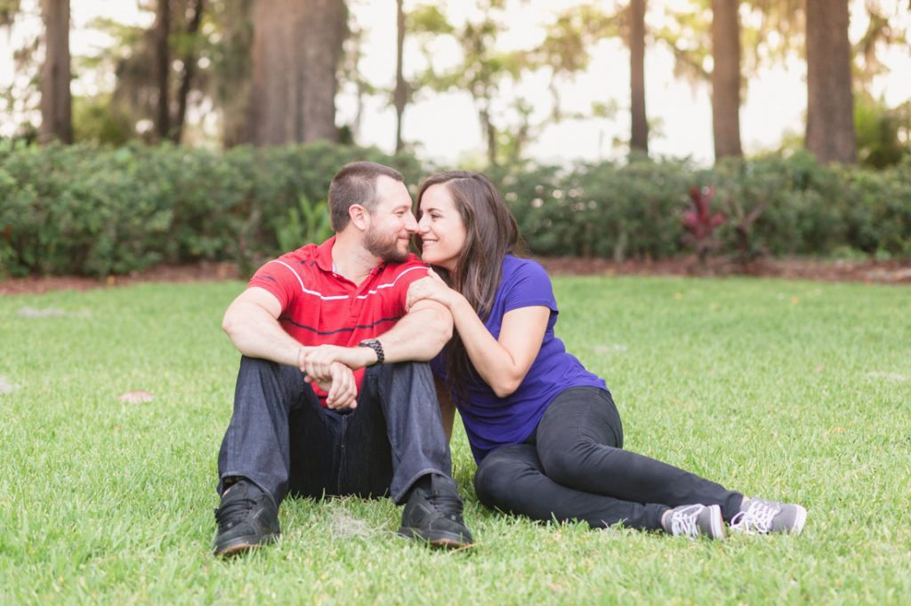 Couple sitting in the grass at their park engagement session at Kraft Azalea gardens captured by top Orlando wedding photographer and videographer
