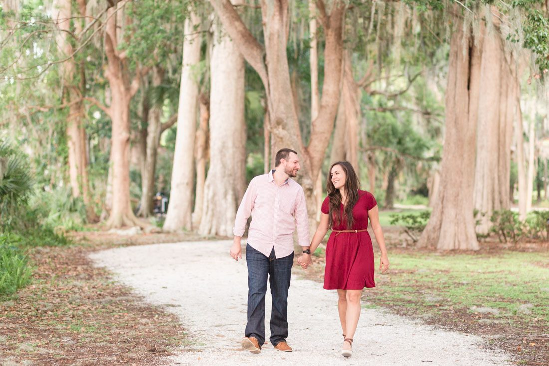 Couple walking through tree lined path at Kraft Azalea gardens for their engagement session with Orlando wedding photographer and videographer