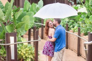Rainy day engagement photography shoot at Disney resort with a couple cuddling under an umbrella captured by top Orlando engagement and proposal photographer