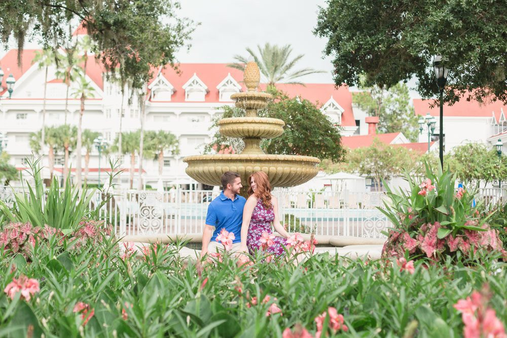 Newly engaged couple poses in front of a fountain at Disney's Grand Floridian Resort during their Orlando engagement photography session