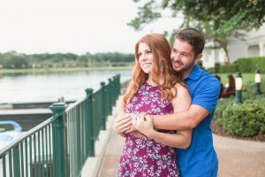 Couples cuddles during their candid engagement photography session with top Disney photographer