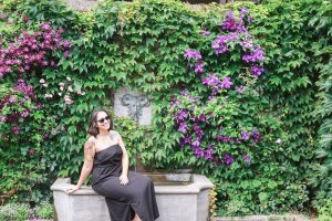 Posing in front of a lush wall of greenery at a garden in Montreal Canada during my travels