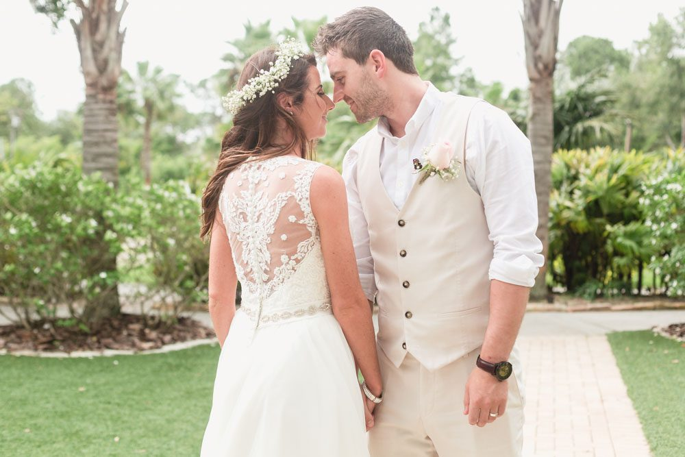 Romantic portrait of the bride and groom during their tropical beach wedding at Paradise Cove captured by top Orlando wedding photographer