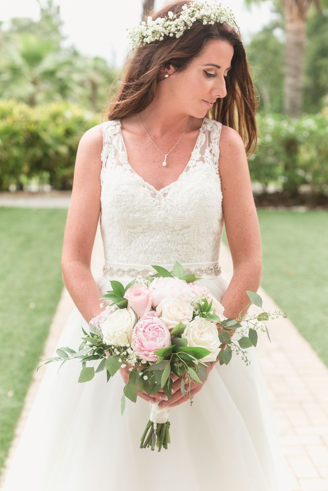 Orlando wedding photographer captures bride holding her beautiful blush pink and cream bouquet at Paradise Cove