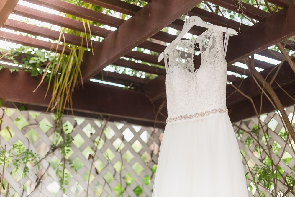 Bride's wedding dress hanging outside her suite at Paradise Cove for her Orlando wedding