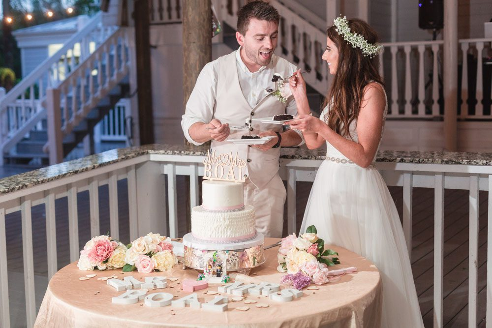Sharing a slice of wedding cake at their reception under the pavilion at Paradise Cove in Orlando Florida