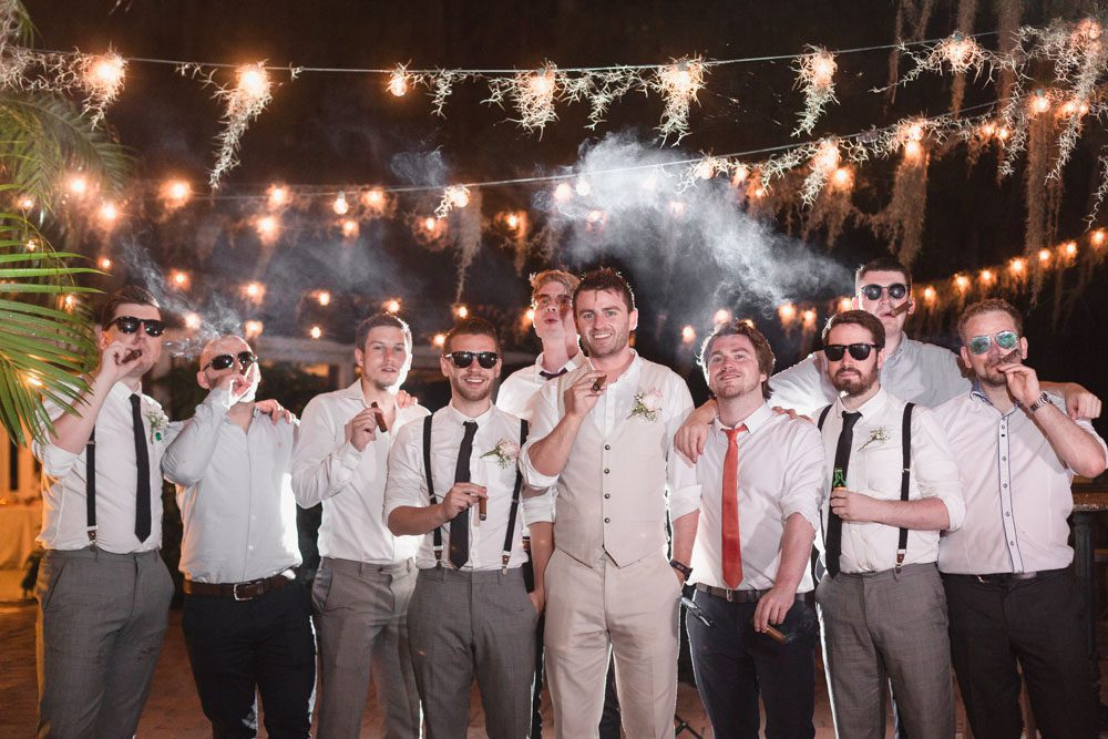 Groom smoking cigars with his groomsmen at his Paradise Cove Orlando wedding day