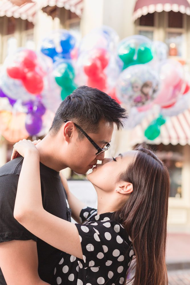Fun photo shoot at Walt Disney World Magic Kingdom park featuring colorful balloons in the background by top Orlando wedding and engagement photographer