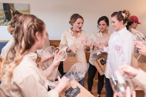 Bridesmaids with custom monogrammed shirts receive a gift from the bride during her country wedding day captured by Orlando wedding photography team