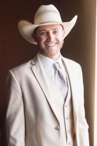 Groom wearing a cowboy hat and grey suit with vest for his country chic wedding day north of Orlando in Central Florida