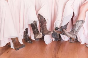Blush pink bridesmaids dresses with cowboy boots for a rustic wedding day captured by top Orlando wedding photographer