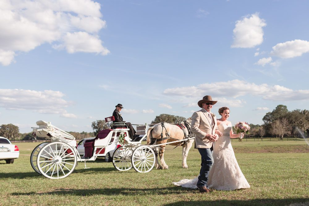 Horse drawn carriage picks up bride for her country chic wedding day at a barn in Central Florida captured by top Orlando photography team