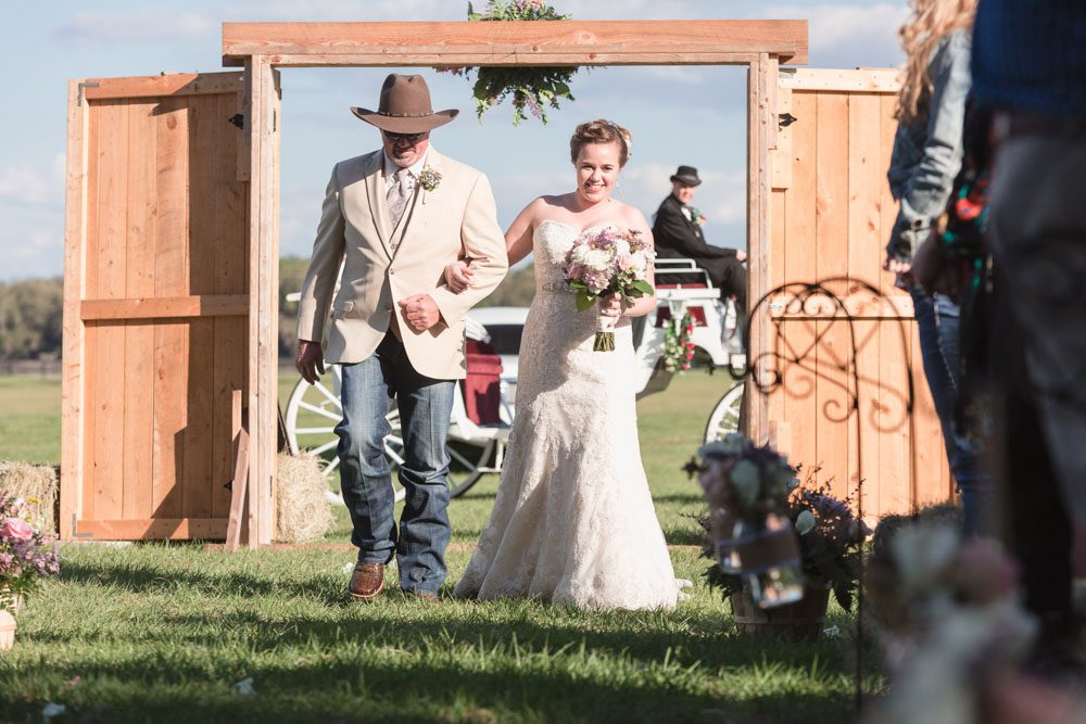 Bride enters through two large barn style doors for her country wedding ceremony in Central Florida