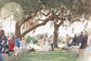 Beautiful outdoor wedding ceremony under a tree with guests sitting on hay bales for a country inspired wedding day in Central Florida