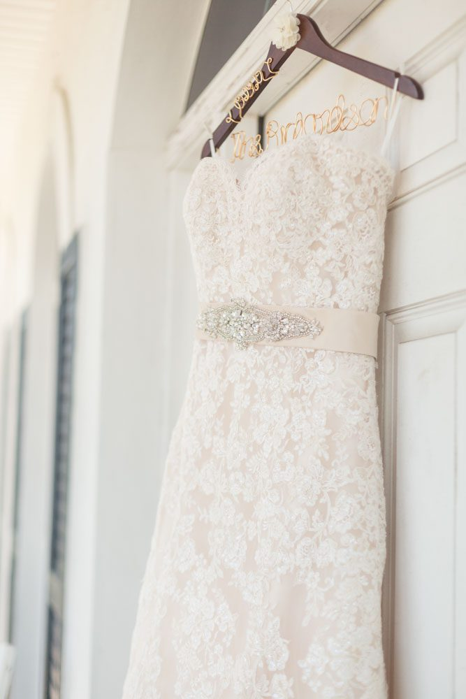 Brides wedding dress hanging in a doorway for a rustic chic country wedding at a barn captured by Orlando wedding photographer and videographer