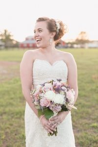Bride wearing a lace dress and holding a purple and pink bouquet for her country rustic wedding day at a barn north of Orlando