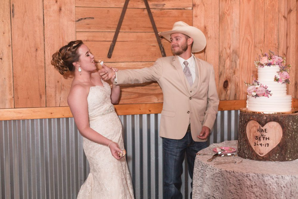 Newlyweds share their first slice of cake by smashing it in each others faces during their barn wedding in Central Florida