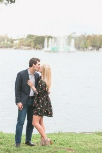 Newly engaged couple kisses in front of the fountain at Lake Eola in downtown Orlando after their surprise proposal is captured by top Orlando photographer