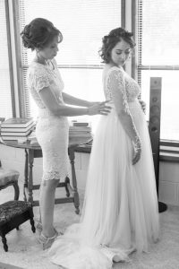 Black and white photography of Bride getting into her wedding dress with her mom during her Kissimmee wedding day